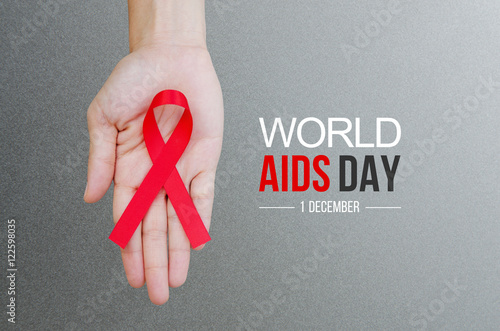 Photo Female hands holding red ribbon HIV, AIDS awareness ribbon