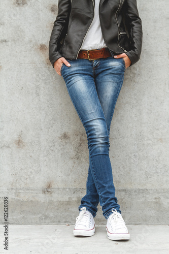 21a3895ea8 Shapely female legs in sneakers and jeans near a concrete wall - Buy ...