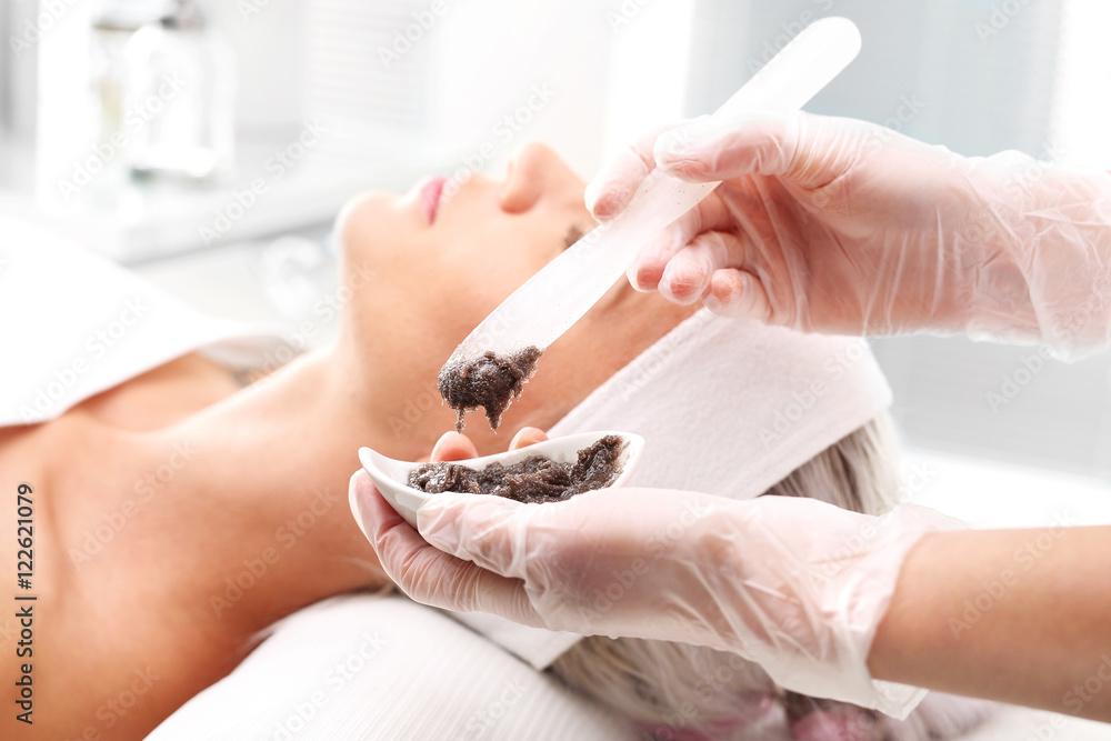 Fototapeta Maseczka oczyszczająca, kobieta w salonie kosmetycznym. Kosmetyczka nakłada maseczkę na twarz kobiety