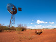 canvas print picture - an old rusty wind turbine and cattle feeder,  in the harsh arid red landscape of the australian outback bush.