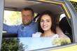 Beautiful couple sitting on backseat in car
