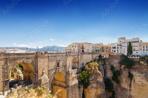 Poster Puente Nuevo and buildings on the cliffside of El Tajo Gorge in Ronda, Malaga province, Spain.