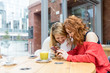 Leinwanddruck Bild - Two young beautiful caucasian blonde and redhead women using smart phone sitting in a bar - technology, social network, communciation concept
