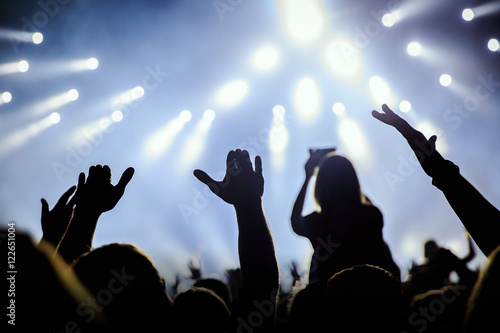 Photo Peope silhouettes of concert crowd in front of bright stage white and blue light