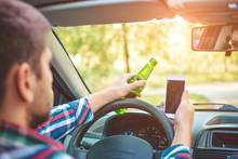 Drunk Young Man Driving A Car With A Bottle Of Beer And Mobile Phone. Don't Drink And Drive Concept. Don't Text And Drive. Driving Under The Influence (DUI), Driving While Intoxicated (DWI)