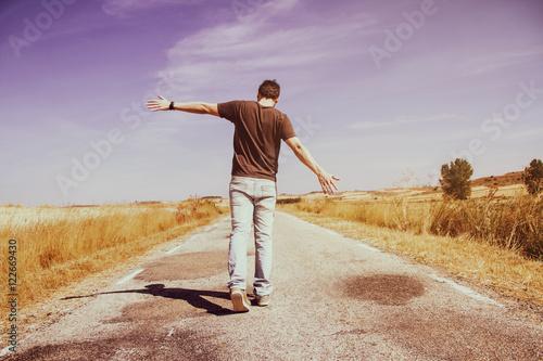 Valokuva  Hombre joven caminando por una carretera vacía