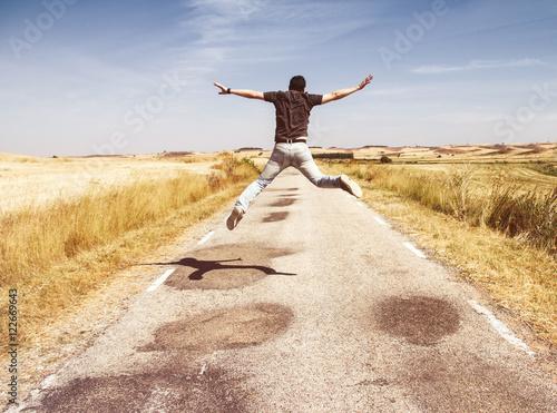 Chico joven saltando de alegría en una carretera vacía en medio del campo