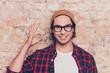 Leinwanddruck Bild - Portrait of cheerful hipster man in glasses gesturing ok
