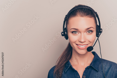 Fototapeta Beautiful consultant of call center in headphones on gray backgr obraz