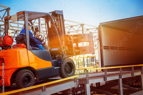 Fotografia Forklift is putting cargo from warehouse to truck outdoors