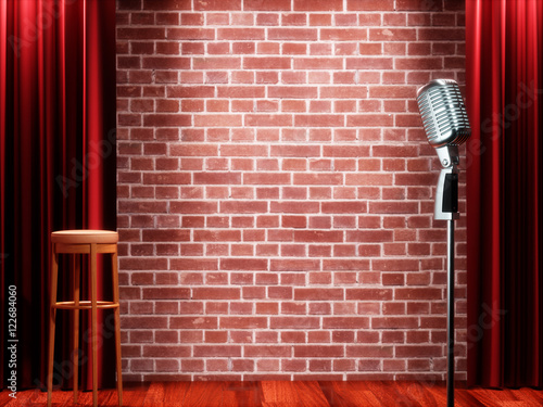 Fotografija  Vintage metal microphone against red curtain on empty theatre stage