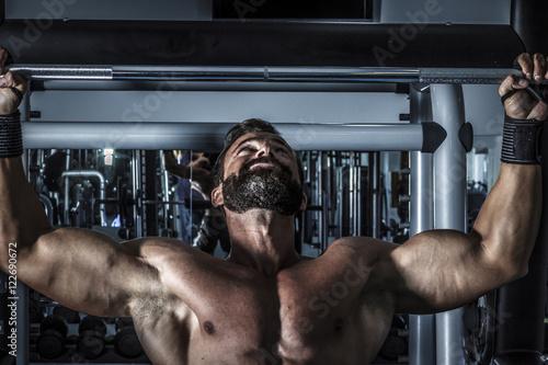 Entrenando en el gimnasio. Hombre con grandes músculos levantando peso mientras entrena en el gimnasio. Ponerse en forma.