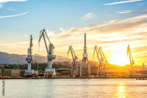 Fototapeta silhouetted cranes at dusk at shipyard