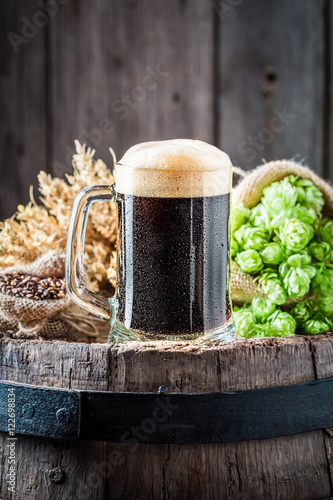 Foto  Pint of fresh dark beer with ingredients