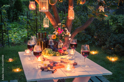 Fototapeta Beautiful table full of cheese and meats in garden at dusk obraz