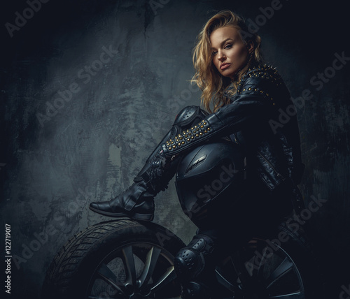 Blonde female in leather clothes sits on a car's wheel .
