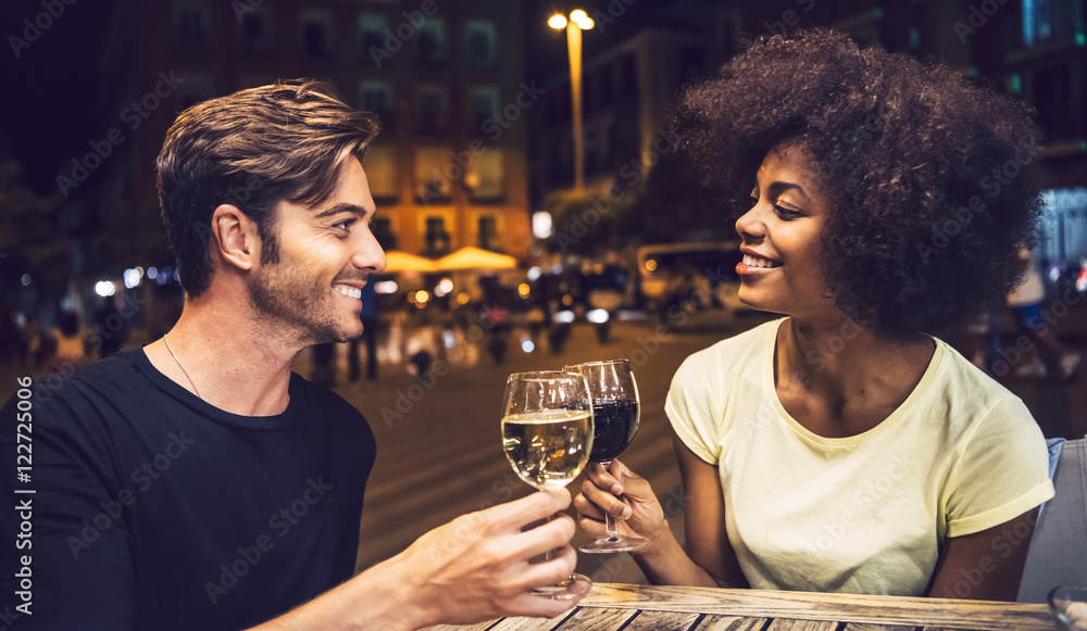 Fototapety, obrazy: Casual interracial couple drinking wine during date