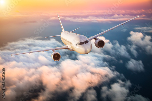 Airplane flying above clouds in dramatic sunset Obraz na płótnie