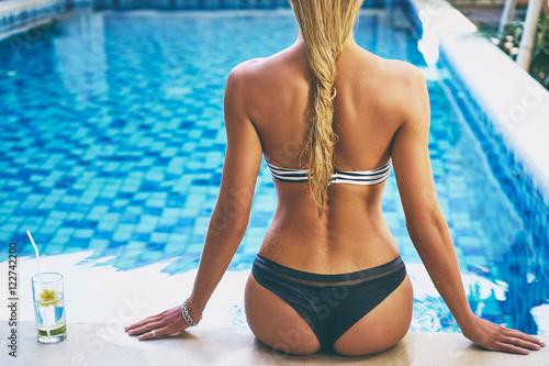 Zdjęcie XXL Cieszyć się wakacjami. Tylny widok pije koktajl w pływackim basenie szczupła młoda kobieta.
