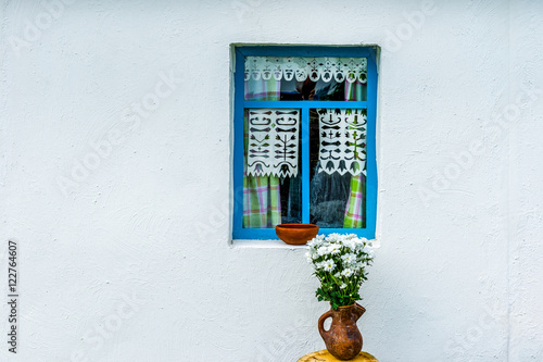 Fotografie, Obraz  White wall of the country peasant house with a blue window. An e