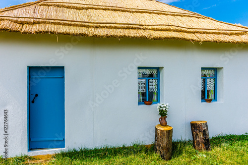 Fotografie, Obraz  View of the peasant house with whitewall and reed roof. A door a