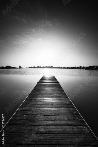 Foto op Aluminium Grijze traf. Black and white photography, pier at sunrise in a park of Manresa,Catalonia, Spain. Nice walking area with trees and water pond