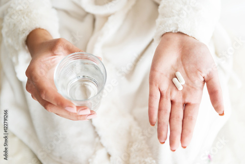 Fotografia  Woman holding a glass of water and pills, detail