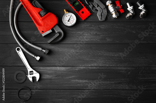 Fotografía  Plumber tools on a gray wooden background