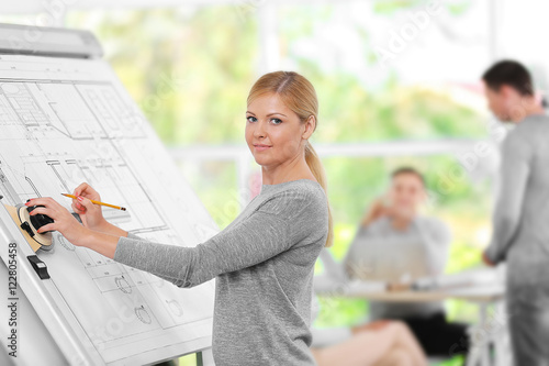 Young female engineer working with architectural project and other engineers on Billede på lærred