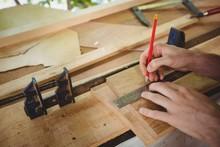 Man Measuring A Wooden Plank