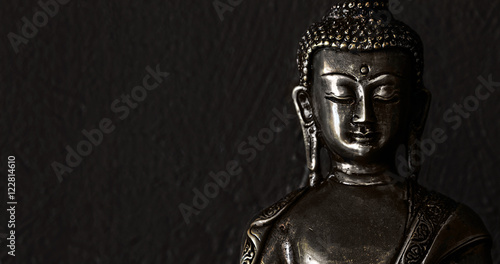 La pose en embrasure Buddha Traditional bronze Buddha statue isolated on black background.