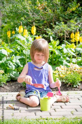 6 year old girl is enjoying gardening Poster