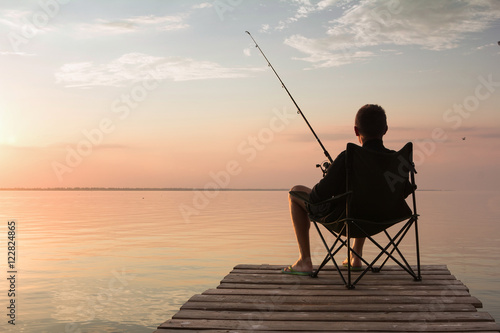 Fototapeta  fisherman with rod over the lake at sunset
