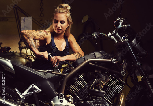 Blond woman mechanic repairing a motorcycle in a workshop Wallpaper Mural