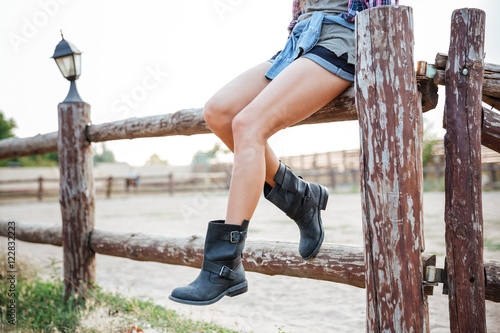 Fotografía  Legs of young woman cowgirl in shorts sitting on fence