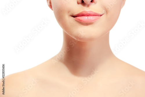 Fotografía  Closeup of young woman's pink lips and neck against white background