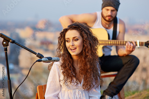 Photo  Young beautiful girl singing with a guitar player outdoor