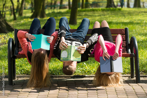 Fotografia  Młodzież czyta książki w parku na ławce