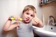 Little boy brushing teeth in bath with electric brush