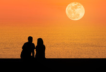 Silhoutte Rear View Romantic Couple Sit Relaxing On The Beach In Sunset  With Full Moon