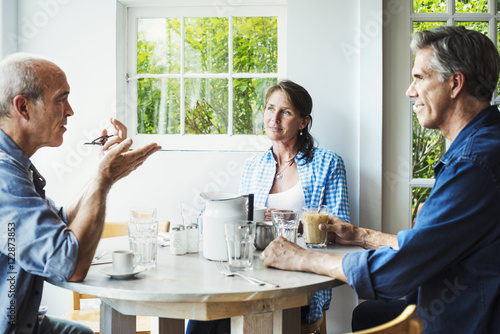 Two men and a woman seated at a coffee shop table talking.
