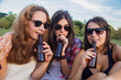 Girls enjoying in the park. They are friends celebrating the holiday having a good time drinking beer in a park. They're happy. They are wearing sunglasses.