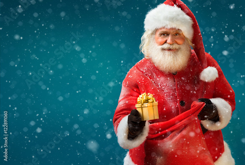 Fotografía  Happy Santa Claus with gift on blue background