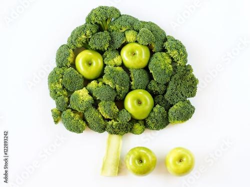 Kompozycja z brokuła i jabłek w kształcie drzewa na białym tle