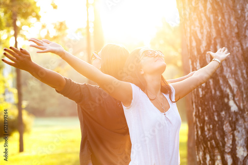 Two beautiful young woman expressing freedom outdoors with her arms outstretched.