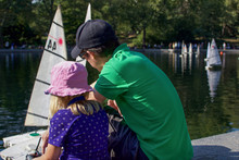 Father And Daughter Playing With Remote Control Sailboat On Central Park Pond In Manhattan New York City