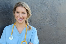 Nurse With Long Blonde Hair And A Stethoscope In A Uniform Smiling At The Camera