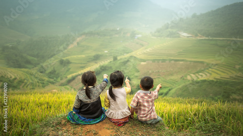 Garden Poster Rice fields Three children sitting side by side, back view to point to Rice