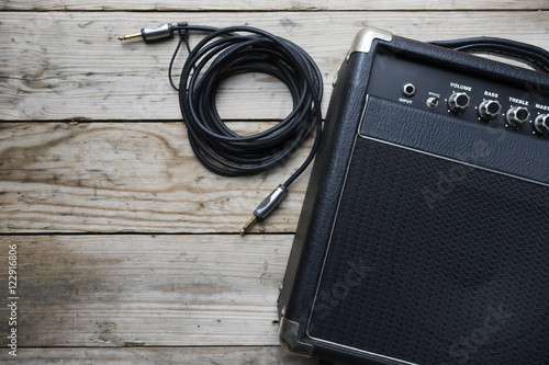 Photo Guitar amplifier and guitar on wood table