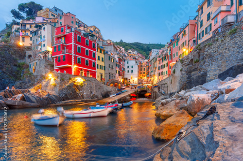 In de dag Liguria Riomaggiore fishing village during evening twilight blue hour, seascape in Five lands, Cinque Terre National Park, Liguria, Italy.